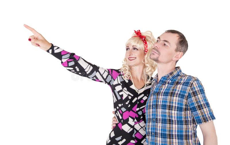Retro coppie divertenti della famiglia che abbracciano e che indicano sull'isolato su immagini stock