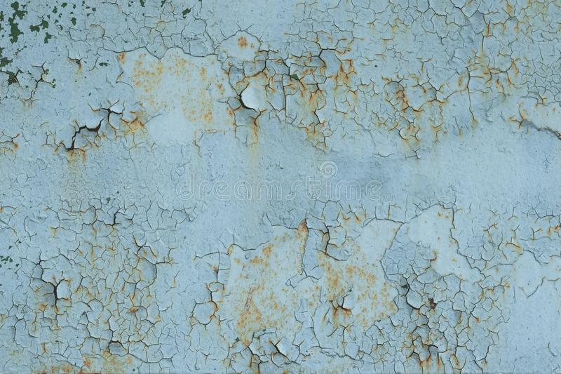 Retro, cracked light blue paint on a rusty door. Abstract background, texture. Stains. Natural pattern of peeling paint on a metal royalty free stock photography