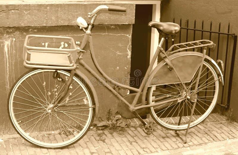 Retro cykel mot en grungy vägg, Amsterdam, Nederländerna arkivbild