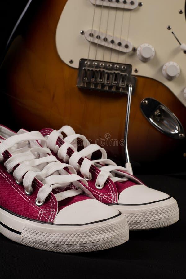 Retro Czerwoni sneakers i zamazana gitara w tle obraz royalty free