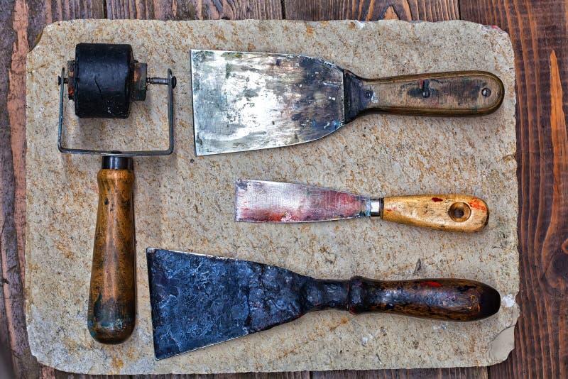 Retro- Design-Tools für Künstlerwerkstatt: Gummirolle, verschiedene Größenkittmesser auf Steinplatte und hölzerner Hintergrund stockbilder