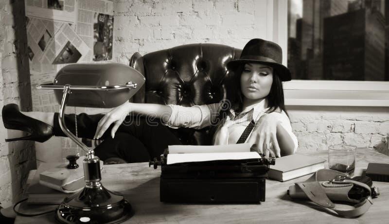 Retro- Detektivmädchen sitzt an einem Tisch stockbilder
