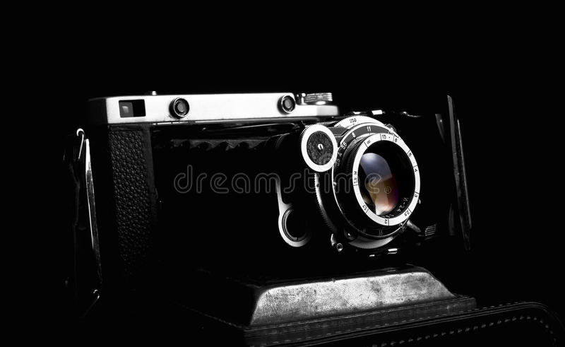 Retro dichte omhooggaand van de fotocamera op de zwarte achtergrond stock foto's
