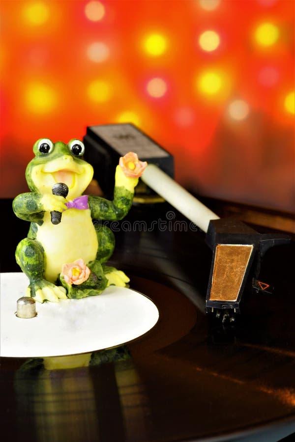 Retro- Disco der Vinylaufzeichnung Musik- und Gesangtöne mit einem Retro- Spieler, auf dem Hintergrund von bunten festlichen Vere stockfotografie