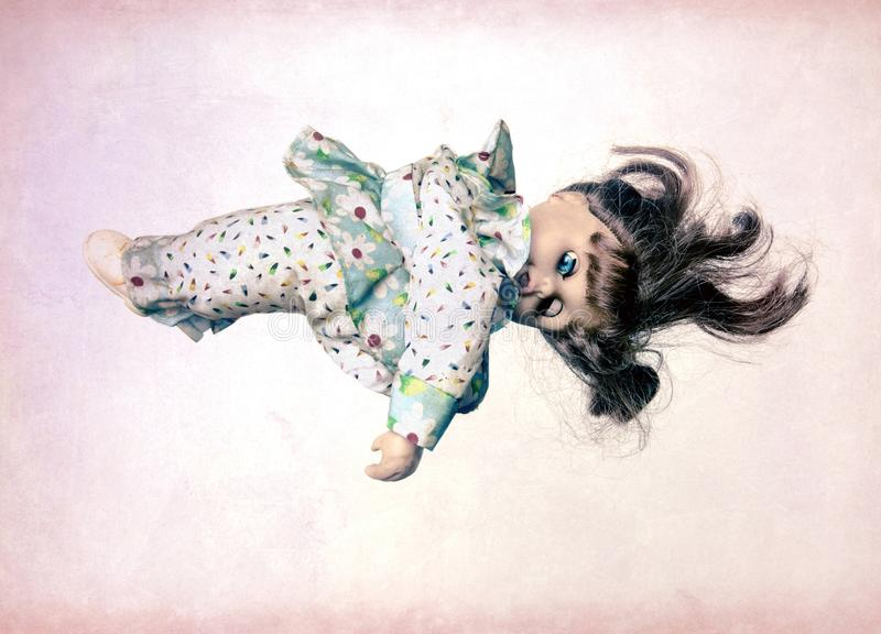 Retro doll levitates with a pink background stock image