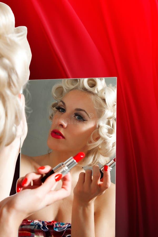 Retro donna che applica rossetto in specchio fotografia stock libera da diritti