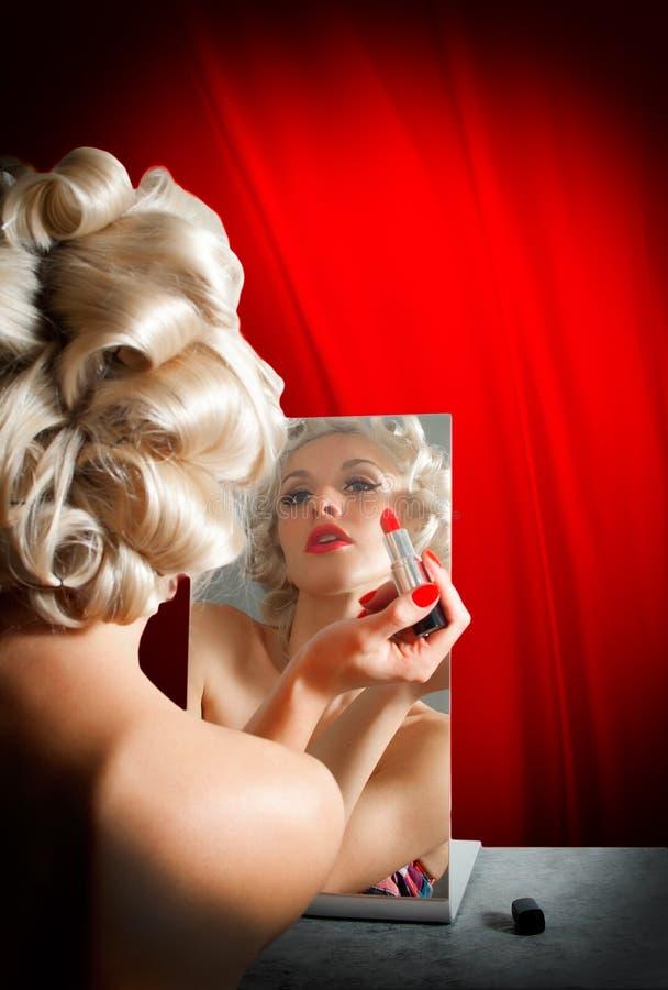 Retro donna che applica rossetto in specchio fotografie stock libere da diritti