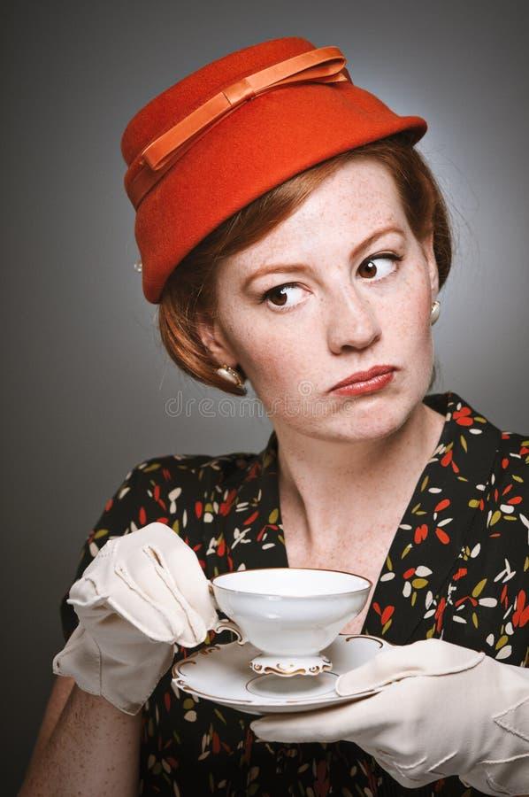 Retro donna che giudica mentre bevendo tè immagine stock libera da diritti