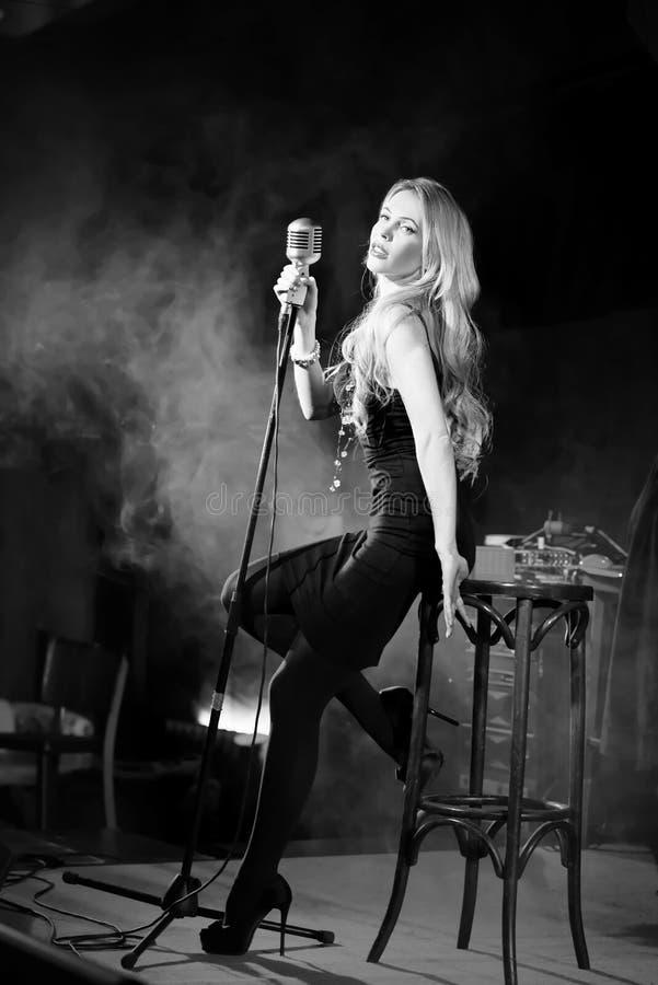 Retro donna elegante attraente, cantante con il mic Stile noir fotografie stock libere da diritti