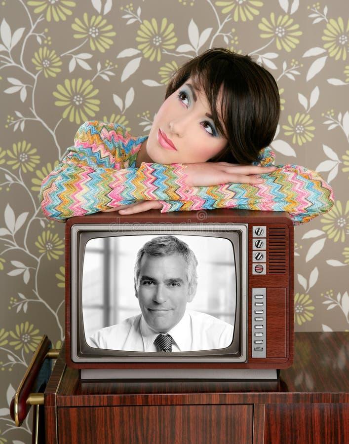 Retro donna nell'amore con l'eroe bello maggiore della TV fotografie stock