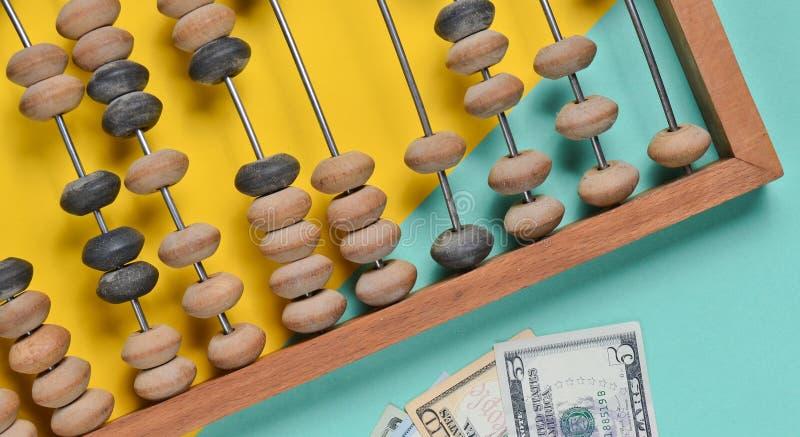Retro drewniany abakus, dolarowi rachunki na barwionym papierowym tle Odgórny widok zdjęcia royalty free
