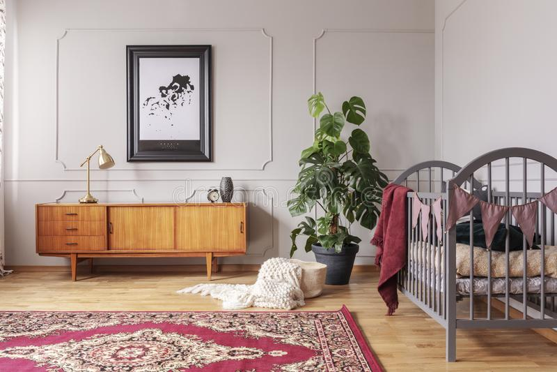 Retro drewniany gabinet w popielatym dziecko sypialni wnętrzu z potwór rośliną w czarnym garnku i drewniany ściąga, istna fotogra obrazy stock