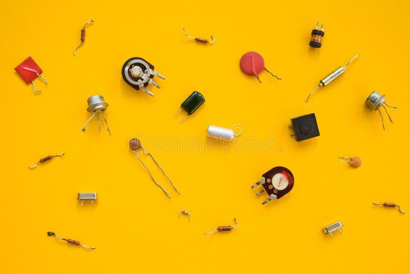 Retro elektronische componenten op gele achtergrond, concept De vlakke samenstelling stock fotografie