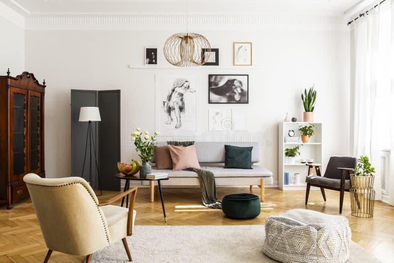 Retro fåtölj och puff på den hemtrevliga mattan i modern vardagsrum som är inre med den grått soffan och tappningmöblemang fotografering för bildbyråer