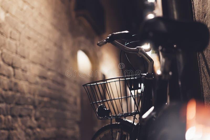 Retro- Fahrrad in der Nachtalten Stadt auf Hintergrund bokeh Lichtaufflackern in der Nachtarchitektur, Weinlesefahrrad in der Abe stockfotografie