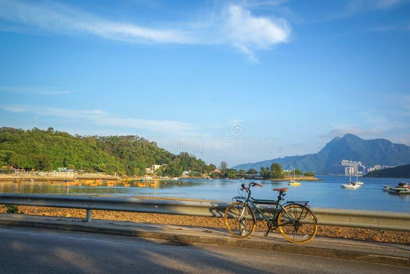 Retro- Fahrrad mit braunem Ledersitz, Berge, See, blauer Himmel stockfotografie