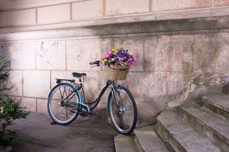 retro fahrrad mit einem korb von blumen an der alten wand. Black Bedroom Furniture Sets. Home Design Ideas