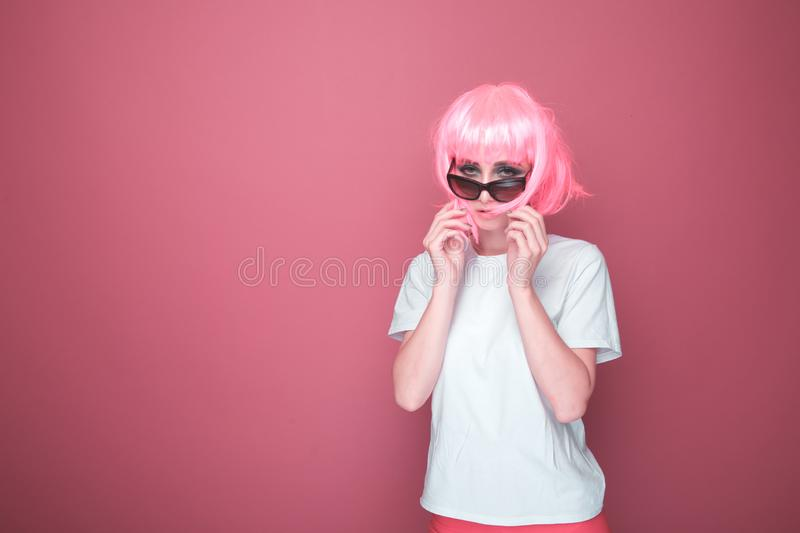 Retro fashion concept. Woman with pink hair in a black glasses and white T-shurt in a bright pink studio. stock photography