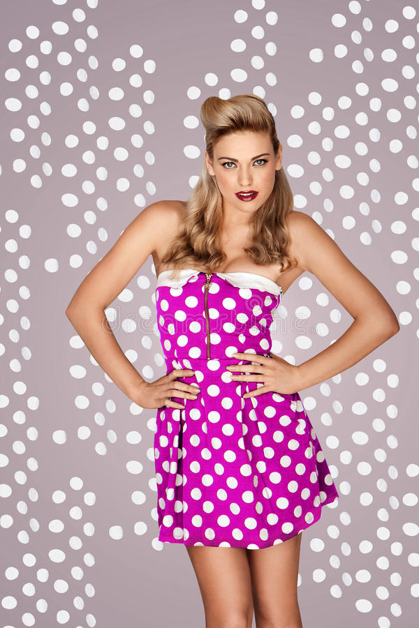 Retro fashion model in polka dot dress. Beautiful blonde retro fashion model in a pink polka dot dress posing in front of a studio background with dots stock photos