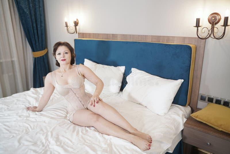 Retro fifties spenderen aantrekkelijk meisje in oude lingerie op witte bedachtergrond - pin-up concept stock fotografie