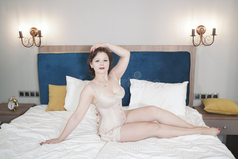 Retro fifties spenderen aantrekkelijk meisje in oude lingerie op witte bedachtergrond - pin-up concept royalty-vrije stock foto's