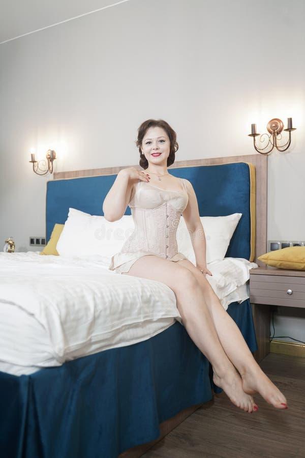 Retro fifties spenderen aantrekkelijk meisje in oude lingerie op witte bedachtergrond - pin-up concept stock foto