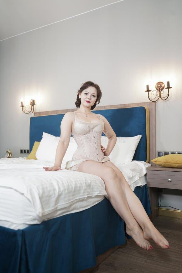 Retro fifties spenderen aantrekkelijk meisje in oude lingerie op witte bedachtergrond - pin-up concept royalty-vrije stock fotografie