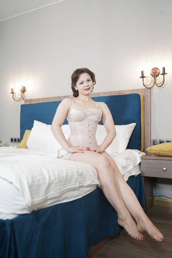 Retro fifties spenderen aantrekkelijk meisje in oude lingerie op witte bedachtergrond - pin-up concept stock afbeelding