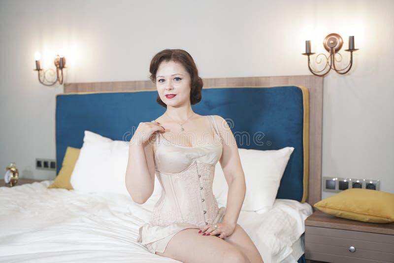 Retro fifties spenderen aantrekkelijk meisje in oude lingerie op witte bedachtergrond - pin-up concept royalty-vrije stock afbeeldingen