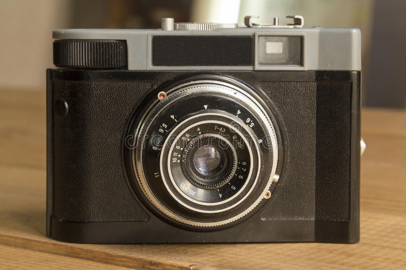 Retro film camera. Black retro film camera on wooden background royalty free stock photos
