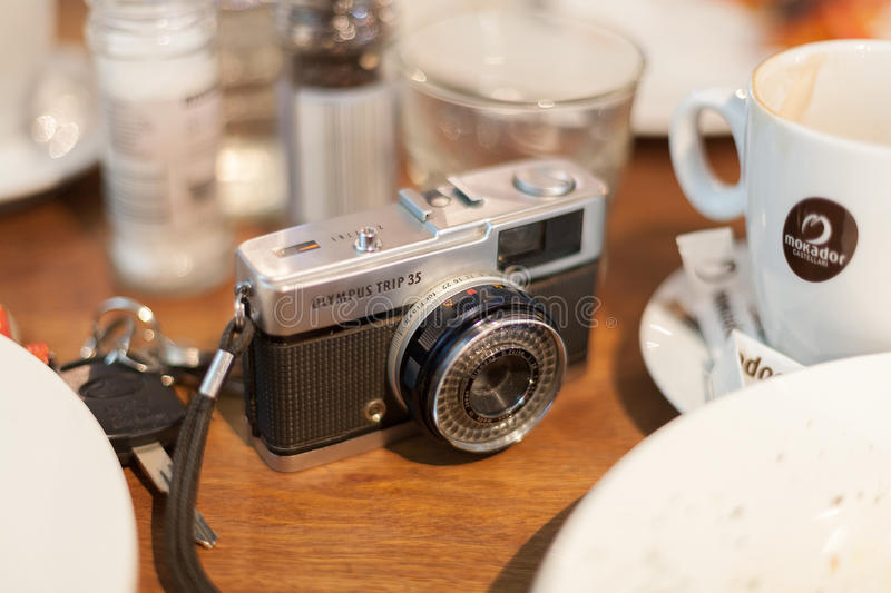 Retro film camera. Canberra, Australia-May 9, 2010. Vintage film camera on a table at a cafe with car keys and coffee cups. The Olympus Trip 35mm camera enjoys royalty free stock photos