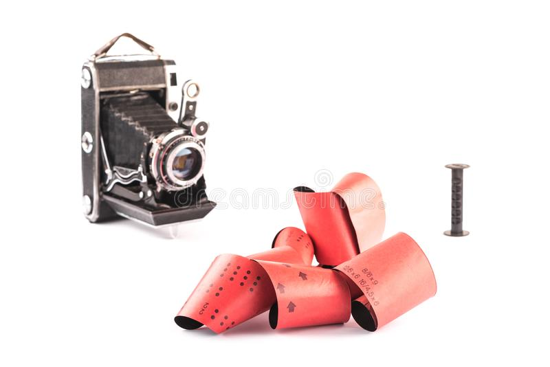 Retro 120 film for medium format retro cameras on white background with shadows, blurry vintage cameras with plastic spool on back stock photo