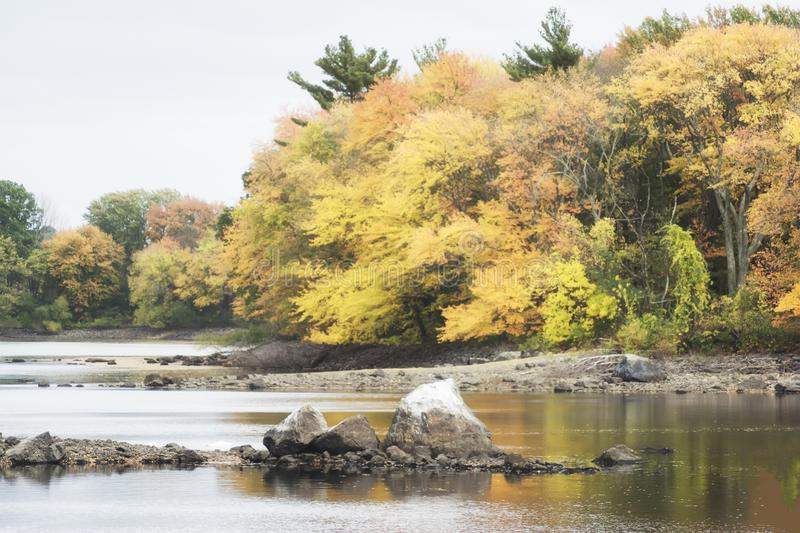 A retro film style photo of a New England lake and forest in the fall.  royalty free stock image