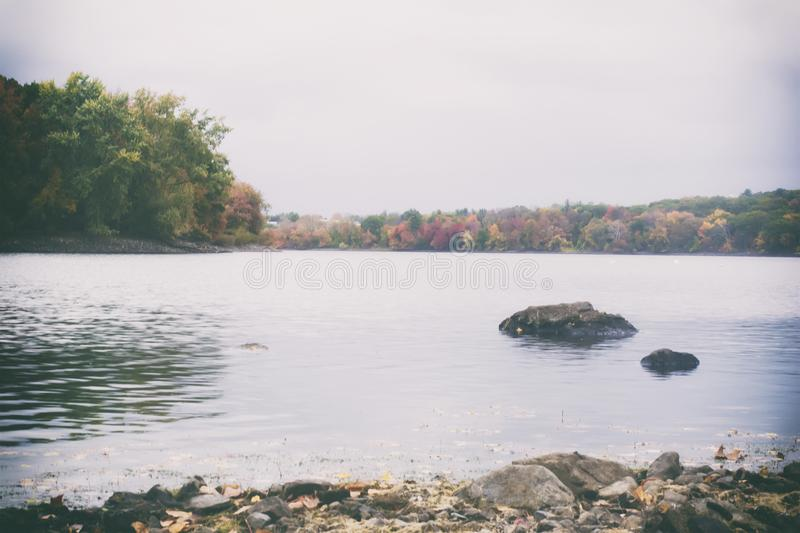 A retro film style photo of a New England lake and forest in the fall.  royalty free stock photo