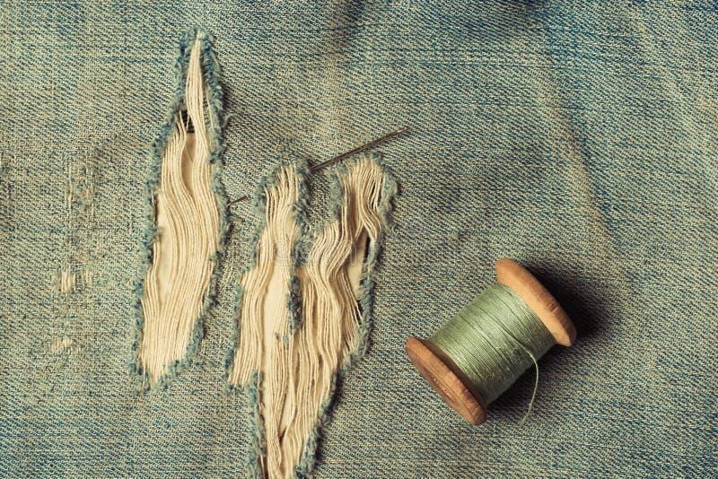 Retro filo della matassa con un ago sui jeans lacerati e sfregati, jeans di cucito, vista superiore, stile d'annata fotografia stock libera da diritti