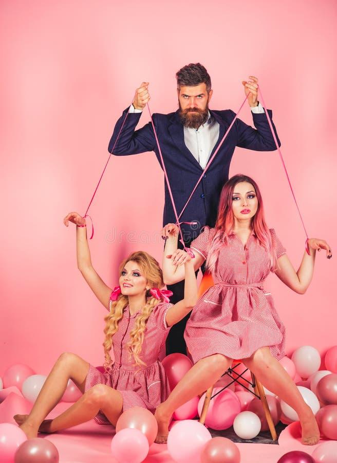 retro flickor och förlage i partiballonger ferier och dockor herravälde och beroende idérik idé Stående av två kvinnor och män so royaltyfria bilder