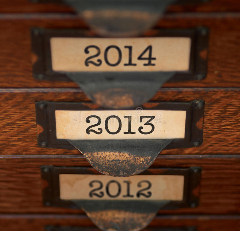 Retro Focus on 2013. Stack of old, oak flat file drawers with years 2012, 2013, and 2014 printed on tags in tarnished brass label holders. Shallow DOF with focus royalty free stock photo
