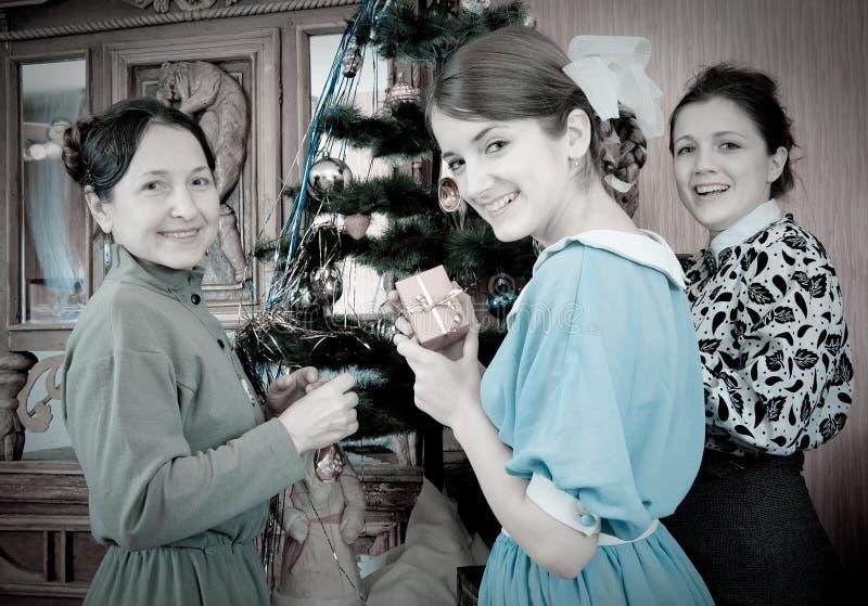 Retro foto delle ragazze con la madre all'albero di Natale immagini stock