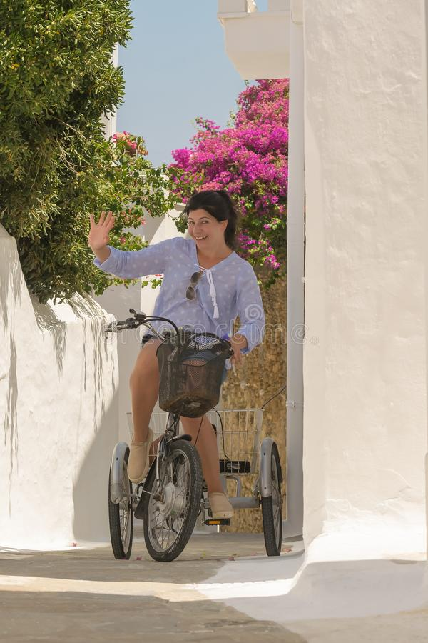 Retro foto med en kvinna överst av en cykel mot en härlig bakgrund fotografering för bildbyråer