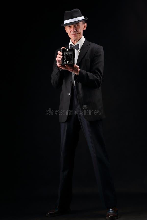Retro fotograf i dräkt och hatt på mörk bakgrund royaltyfria bilder