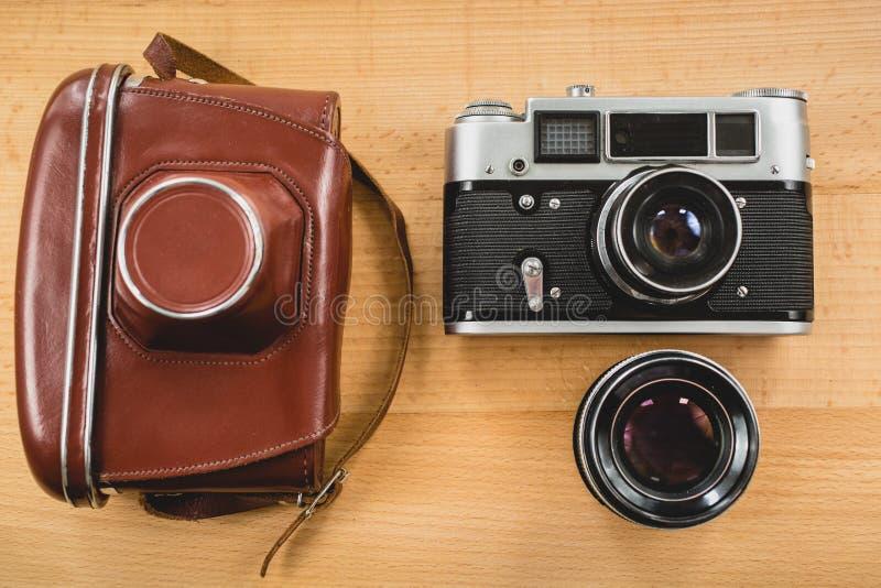 Retro fotografiuppsättning av kameran, fallet och linsen på träbackgro fotografering för bildbyråer