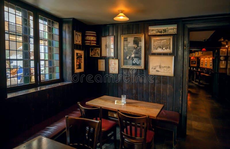 Retro- Fotos und Weinlesemöbel innerhalb des klassischen Artrestaurants mit Holztischen lizenzfreie stockfotografie