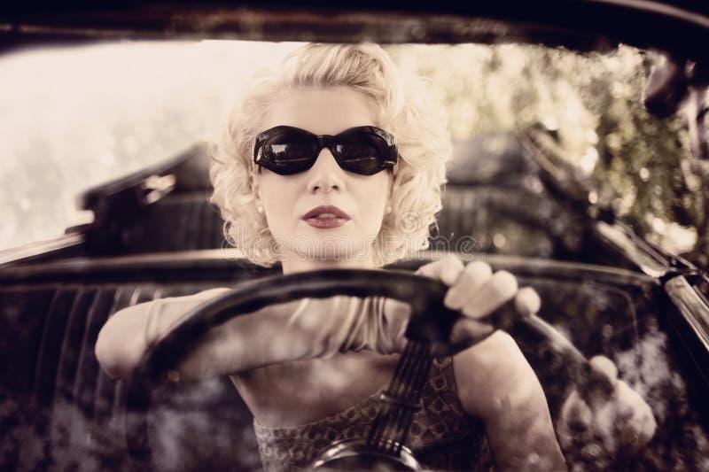 Retro- Frau, die ein Auto antreibt lizenzfreies stockbild