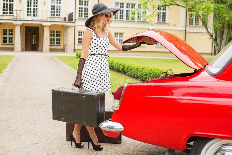 Retro- Frau, die Koffer in Weinleseauto einsetzt stockbild