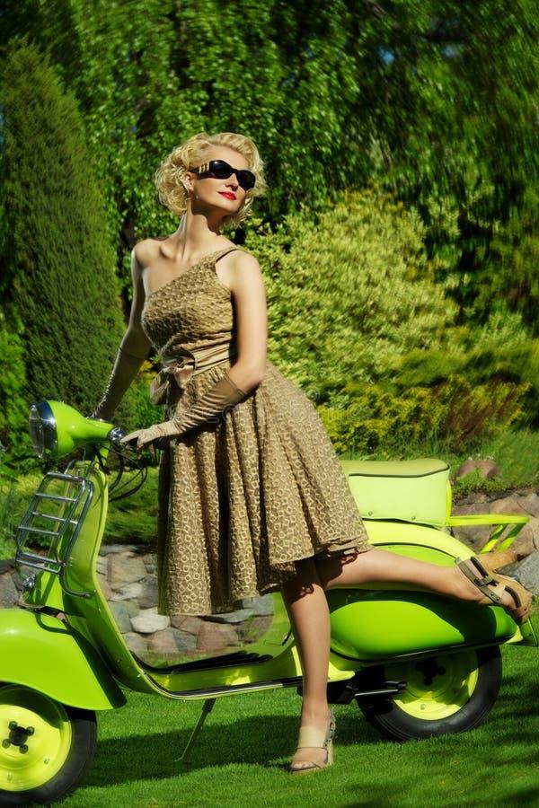 Retro- Frau draußen mit einem grünen Roller stockbild