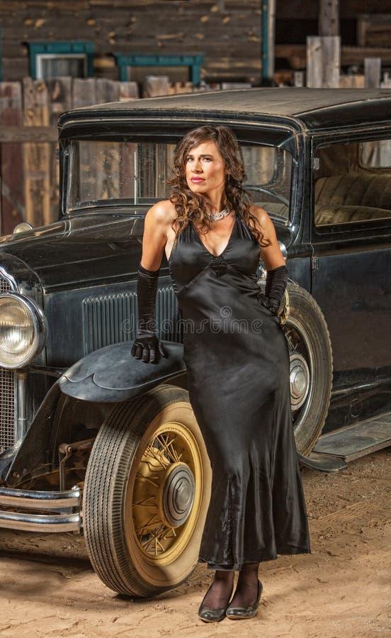 Retro- Frau nahe altem Auto stockbild