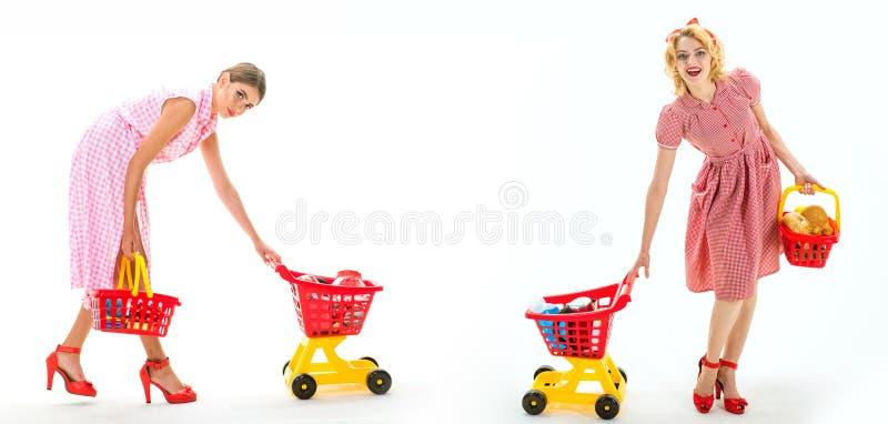 Retro- Frauen gehen mit vollem Warenkorb Einsparungen auf Käufen On-line-Einkaufsapp Glückliche Einkaufsmädchen mit vollem Warenk lizenzfreie stockfotos