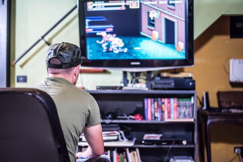 Retro gamer voor TV stock fotografie