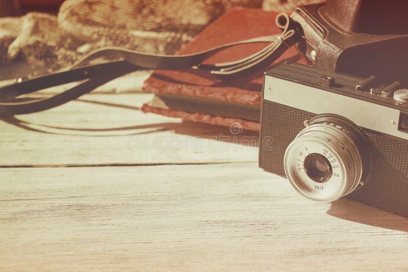 Retro gammal kamera med det svarta läderfallet och sammettappningfoto på vitt träbakgrundskopieringsutrymme royaltyfria bilder