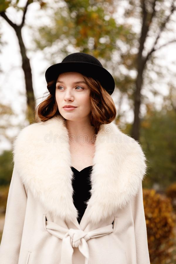 Retro gangster girl in black hat and coat in autumn park looks aside royalty free stock photography